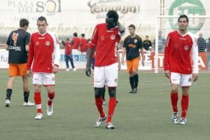 Los deportivistas Pierre, Diop y Raúl Rodríguez se van a los vestuarios tras consumarse el descenso del Eivissa a Tercera División.  JUAN A. RIERA