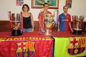 Foto para el recuerdo. Los aficionados azulgranas de Ciutadella posaron ante los trofeos de Copa del Rey, Liga y Champions