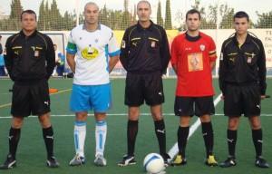 El trío arbitral con los capitanes del partido