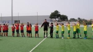 El arbitro con ambos equipos al inicio del partido