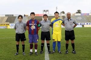 El trio arbitral con los capitanes del partido