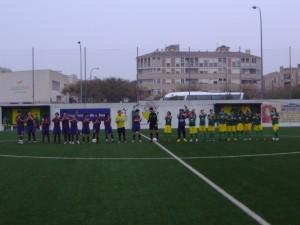 Ambos equipos con el arbitro al inicio del partido